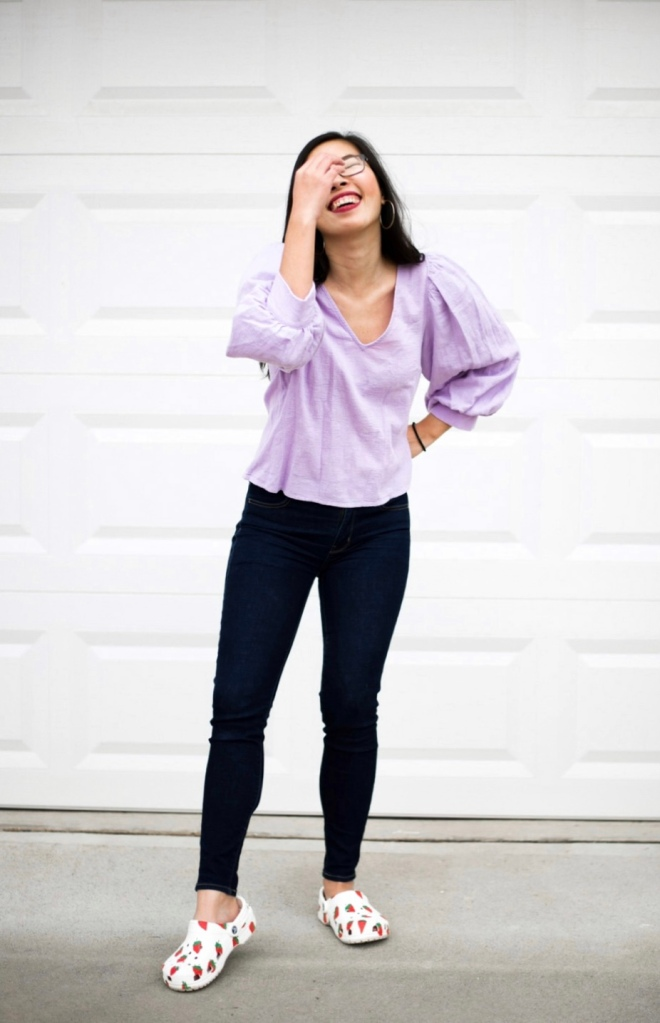 A woman standing wearing a lilac shirt, dark jeans, and strawberry crocs.